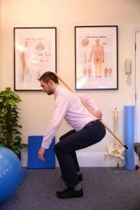 Chiropractor shows correct bending technique for back pain and sciatica