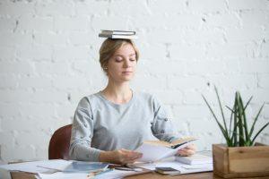 lady sitting upright balancing book on head